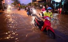 Đoàn người dắt bộ xe về nhà trong cảnh nước ngập nửa bánh