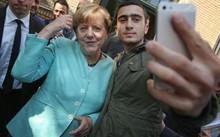 Anas Modamani chụp hình chung với bà Merkel. Ảnh: Independent
