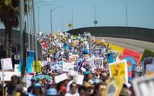 Người biểu tình giơ cao biểu ngữ, diễu hành dọc đường cao tốc ở thành phố Los Angeles, bang California, bờ tây nước Mỹ. Ảnh: A