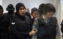 Đoàn Thị Hương (phải) được cảnh sát hộ tống tới ga KLIA2 tại sân bay ở Sepang, Malaysia, ngày 24/10. Ảnh: AP