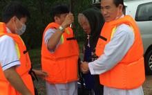 Các cán bộ y tế huyện Phú Vang vào vùng lũ đón bệnh nhân hơn 80 tuổi bị cao huyết áp do trạm y tế xã chuyển lên. (Ảnh Vân Triều)