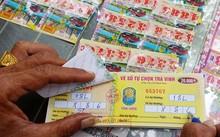 """Một người đến điểm vé số tự chọn ở tỉnh Trà Vinh mua """"số đề"""" bao 18 lô. Anh này chọn 2 số cuối 86 để dò kết quả mở thưởng chiều 30/11 của Công ty XSKT Sóc Trăng. Ảnh: Việt Tường."""