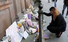 Một phụ nữ đặt hoa tưởng nhớ nạn nhân vụ tấn công ở nhà thi đấu Manchester, trung tâm thành phố. Ảnh: Reuters