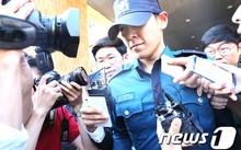Hình ảnh T.O.P rời trụ sở cảnh sát hôm 5/6. Ảnh: News1.