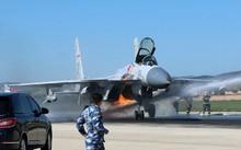 Lính cứu hỏa dập lửa phát ra từ động cơ chiếc J-15. Ảnh: Weibo.