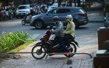 Dù gắn barie nhưng người dân đi xe máy vẫn cố leo lên vỉa hè.