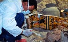 Thành viên của đoàn khảo cổ Ai Cập xem xét quan tài bằng gỗ hôm 18/4. Ảnh: Getty.