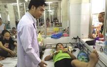 BS Phan Minh Trí kiểm tra chức năng vận động chân của bé Th. sau mổ. Ảnh: K.Q .