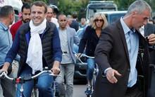 Tổng thống Pháp Emmanuel Macron (trái) cùng phu nhân Brigitte Trogneux (giữa) đạp xe rời nhà riêng ngày 10/6 ở Le Touquet trong dịp về đây nghỉ cuối tuần và đi bỏ phiếu Quốc hội - Ảnh: Reuters