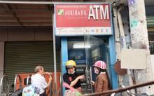 Một số ngân hàng đã đưa ra quy định dừng giao dịch tại các cây ATM vào ban đêm nhằm đề phòng tội phạm thẻ sau khi xảy ra một số vụ chủ thẻ mất tiền trong tài khoản lúc nửa đêm. Trong ảnh: người dân rút tiền tại trụ ATM Agribank trên đường Nơ Trang Long, Q