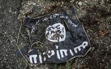 Cờ của IS bị đất đá vùi lấp trong khu vực xung đột. Ảnh: Sputnik
