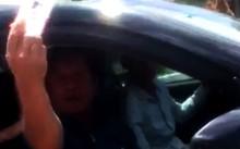 """Người đàn ông ngồi trong xe còn giơ """"thẻ ngành"""" ra để dọa CSGT - Ảnh chụp từ clip"""