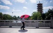Một phụ nữ che dù đi trong nắng nóng gay gắt ở Thượng Hải - Ảnh: AFP