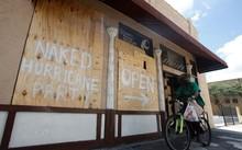 """Người dân """"trang trí"""" các tấm gỗ dùng để gia cố cửa bằng những thông điệp hài hước: """"Tiệc đón bão khỏa thân mở cửa lối này"""". Ảnh: Reuters."""