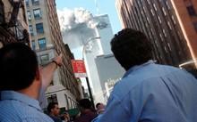 Người đi đường chỉ lên toà Trung tâm Thương mại Thế giới bốc cháy. Ảnh: Reuters