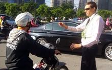 Ông Tây ra hiệu người đi xe máy dừng lại trên Xa lộ Hà Nội để nhường dòng xe đổ vào đường Võ Trường Toản. Ảnh: Sơn Hòa