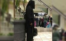 Người đàn ông Mỹ mặc trang phục đen có mũ trùm đầu, hai tay cầm túi và súng trường giả ở trung tâm thương mại bang Nebraska. Ảnh: Twitter.