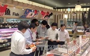 Đại diện Bộ Công Thương và cán bộ phụ trách siêu thị AEON Nhật Bản xem mặt hàng cá tra Việt Nam. Ảnh: Thành Hữu/Phóng viên TTXVN tại Nhật Bản