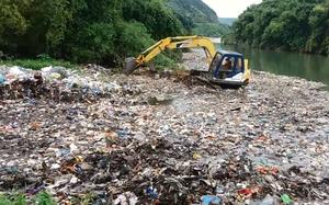 Chiếc máy xúc đang cào rác đổ xuống suối.