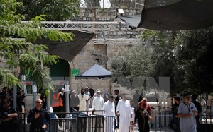 Các tín đồ Hồi giáo đi qua máy dò kim loại tại khu vực lối vào đền thờ Al-Aqsa ở Jerusalem ngày 23/7. (Nguồn: AFP/TTXVN)