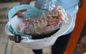 Các tài xế bỏ tiền lẻ vào chai nhựa để mua vé qua trạm BOT Cai Lậy.