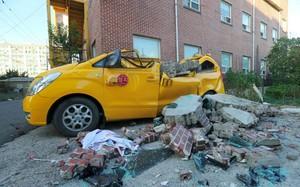Xe ô tô bị gạch đá phá hủy do động đất. Ảnh: YONHAP