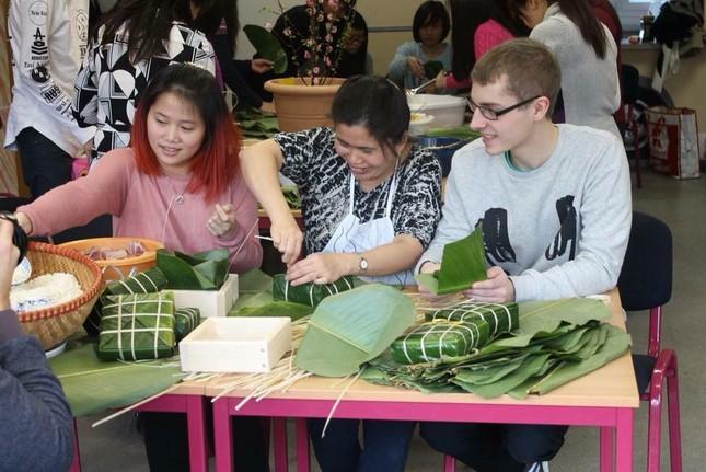 Chị Thanh Vân (giữa) cùng các bạn ngoại quốc làm bánh chưng