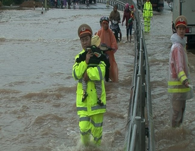 Cảnh sát giao thông bế trẻ qua đoạn nước lụt - ảnh 2