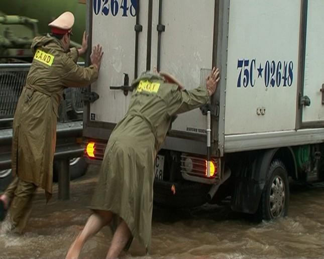Cảnh sát giao thông bế trẻ qua đoạn nước lụt - ảnh 1