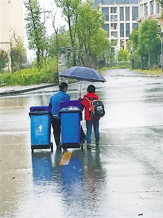 Cậu bé che ô, giúp đỡ người lao công giữa trời mưa gió gây xúc động - ảnh 1