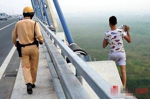 Hà Nội: Nam thanh niên ôm tảng bê tông đòi nhảy xuống cầu Nhật Tân tự tử - anh 1