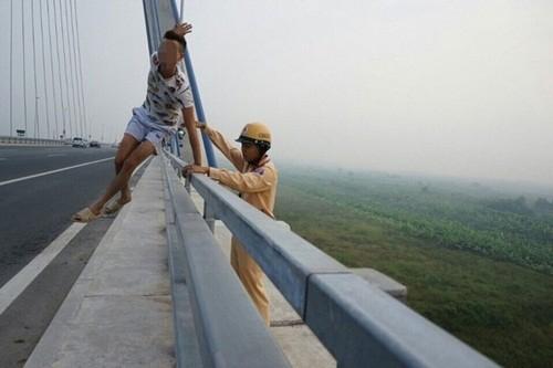 Hà Nội: Nam thanh niên ôm tảng bê tông đòi nhảy xuống cầu Nhật Tân tự tử - anh 3