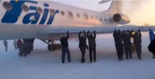 74 hành khách dùng tay đẩy máy bay bị đóng băng trong nhiệt độ -52 độ - anh 1