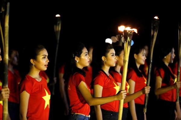 Ngắm thí sinh hoa hậu Việt Nam áo đỏ in sao vàng cầm đuốc chạy bên bờ biển - anh 4